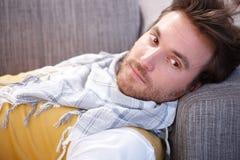 Uomo bello che pone sul sofà che daydreaming immagini stock