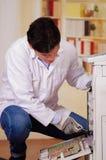 Uomo bello che ripara una fotocopiatrice durante la manutenzione facendo uso dei guanti d'uso di un lavoro del cacciavite Fotografie Stock