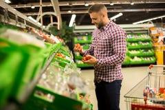 Uomo bello che sceglie i pomodori freschi in supermercato fotografia stock