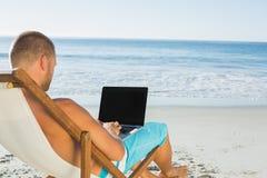 Uomo bello che scrive sul suo computer portatile mentre sedendosi sulla sua piattaforma chai Fotografia Stock
