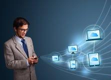 Uomo bello che scrive sullo smartphone con la computazione della nuvola Immagini Stock Libere da Diritti