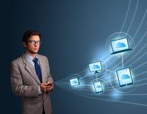 Uomo bello che scrive sullo smartphone con la computazione della nuvola Immagine Stock