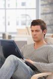 Uomo bello che si concentra sullo schermo del computer portatile Immagine Stock Libera da Diritti