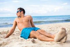 Uomo bello che si distende sulla spiaggia Immagine Stock