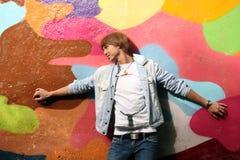 Uomo bello che si leva in piedi la parete vicina dei graffiti Fotografia Stock Libera da Diritti