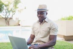 Uomo bello che si rilassa nel suo giardino facendo uso del computer portatile fotografia stock libera da diritti