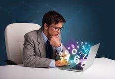 Uomo bello che si siede allo scrittorio e che digita sul computer portatile con il numero 3d Immagini Stock