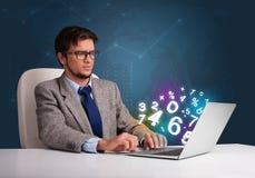 Uomo bello che si siede allo scrittorio e che digita sul computer portatile con il numero 3d Fotografie Stock