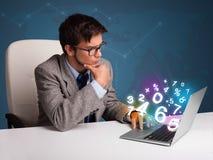 Uomo bello che si siede allo scrittorio e che digita sul computer portatile con il numero 3d Fotografia Stock
