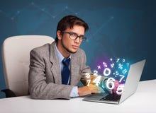 Uomo bello che si siede allo scrittorio e che scrive sul computer portatile con il numero 3d Fotografia Stock