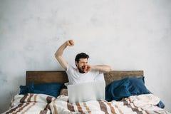 Uomo bello che si siede a letto e che allunga Immagine Stock