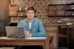 Uomo bello che si siede nel luogo di lavoro con il computer portatile Immagini Stock