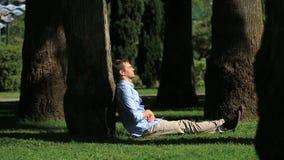 Uomo bello che si siede sotto una palma e che passa in rassegna Internet su uno smartphone video d archivio