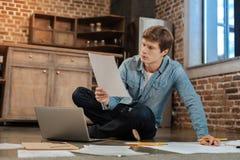 Uomo bello che si siede sul pavimento e che legge documento Immagine Stock