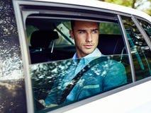 Uomo bello che si siede in un'automobile con il computer della compressa fotografia stock