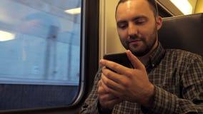 Uomo bello che si siede in una metropolitana e che pratica il surfing nel web con il suo smartphone archivi video