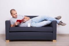 Uomo bello che si trova sul sofà e sul libro di lettura con la tazza di tè Immagine Stock Libera da Diritti