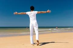 Uomo bello che sta al sole sulla spiaggia Immagine Stock