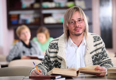 Uomo bello che studia allo scrittorio con i lotti dei libri Fotografie Stock