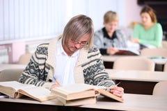 Uomo bello che studia mentre sedendosi allo scrittorio con il lotto dei libri Immagini Stock
