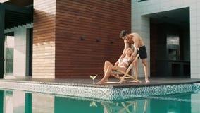 Uomo bello che tocca donna vicino alla piscina alla casa di lusso archivi video