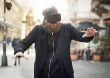 Uomo bello che usando i vetri alta tecnologia di realtà virtuale all'aperto Fotografie Stock