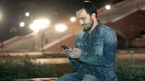 Uomo bello che utilizza il cellulare dello Smart Phone nella città stock footage