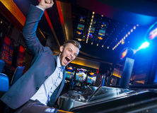 Uomo bello che vince alle slot machine Fotografia Stock