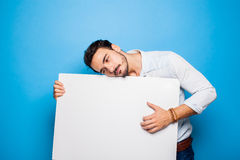 Uomo bello con casuale della barba vestito tenendo un pannello in bianco sopra Fotografie Stock Libere da Diritti