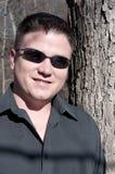 Uomo bello con gli occhiali da sole nel legno Immagini Stock