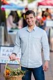 Uomo bello con il canestro al mercato degli agricoltori Fotografia Stock Libera da Diritti