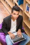 Uomo bello con il computer portatile in biblioteca Fotografia Stock Libera da Diritti