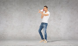 Uomo bello con il megafono sopra il muro di cemento Fotografia Stock Libera da Diritti