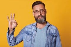 Uomo bello con il rivestimento d'uso del denim della barba ed i supporti grigi della maglietta contro la parete gialla dello stud immagini stock