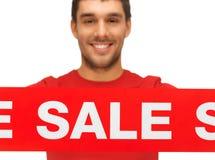 Uomo bello con il segno di vendita Fotografia Stock Libera da Diritti