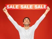 Uomo bello con il segno di vendita Fotografia Stock
