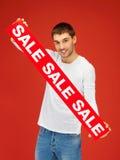 Uomo bello con il segno di vendita Immagine Stock