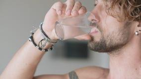 Uomo bello con l'acqua ghiacciata bevente del petto nudo dal vetro e dallo sguardo fuori della finestra della stanza archivi video
