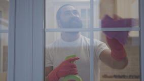 Uomo bello con la bella barba dei pantaloni a vita bassa che pulisce la finestra in guanti con il detersivo nella sua nuova casa  archivi video