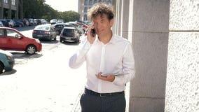 Uomo bello con la camicia bianca che parla sul telefono che cammina con la compressa che ride colpo medio archivi video