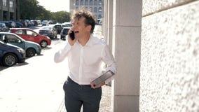 Uomo bello con la camicia bianca che parla sul telefono che cammina con la risata della compressa stock footage