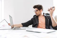 Uomo bello concentrato in occhiali che parla dallo smartphone fotografie stock libere da diritti
