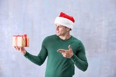 Uomo bello in contenitore di regalo della tenuta del cappello di Natale Immagini Stock