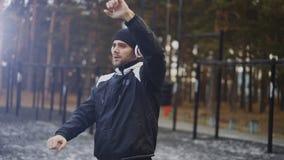 Uomo bello in cuffie che fanno allungando esercizio mentre musica d'ascolto nel parco di inverno Fotografia Stock