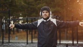 Uomo bello in cuffie che fanno esercizio di riscaldamento mentre musica d'ascolto nel parco di inverno Fotografia Stock Libera da Diritti