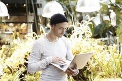 Uomo bello dei pantaloni a vita bassa che lavora al computer portatile all'aperto in parco Giorno soleggiato del ritratto maschio Fotografia Stock