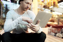 Uomo bello dei pantaloni a vita bassa che lavora al progetto start-up sul computer portatile portatile Tipo nello sguardo in avan Immagini Stock Libere da Diritti