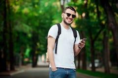 Uomo bello dei pantaloni a vita bassa che per mezzo dello Smart Phone Immagini Stock