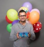 Uomo bello dei pantaloni a vita bassa con i baloons e un presente in studio Fotografia Stock