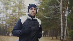 Uomo bello del corridore in cuffie che pareggiano mentre musica d'ascolto nel parco di inverno di mattina Immagini Stock